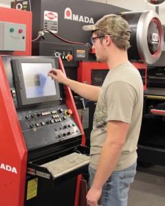 An operator programs a turret press.
