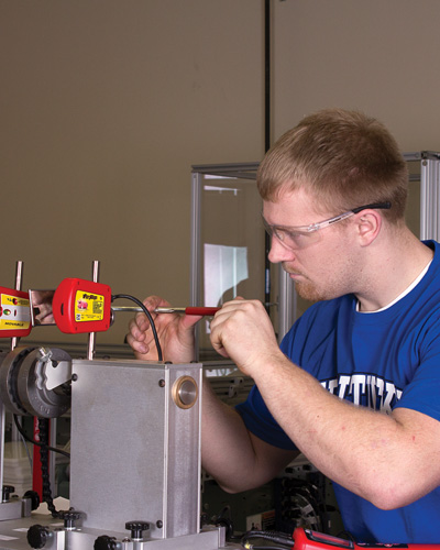 A technician checks the precision shaft alignment on a chain drive.