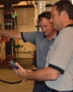 Technicians inspect a commercial chiller to repair or replace components before failure occurs.