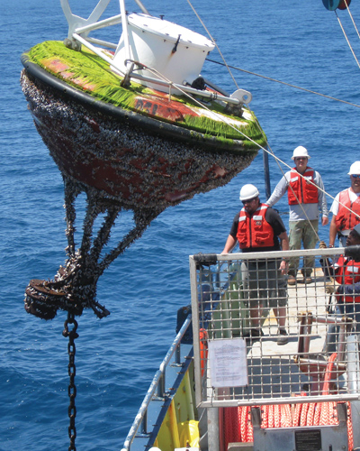 Marine technicians retrieve an oceanographic buoy.