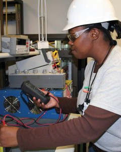 A nuclear technician tests electric circuits during a plant shut-down.